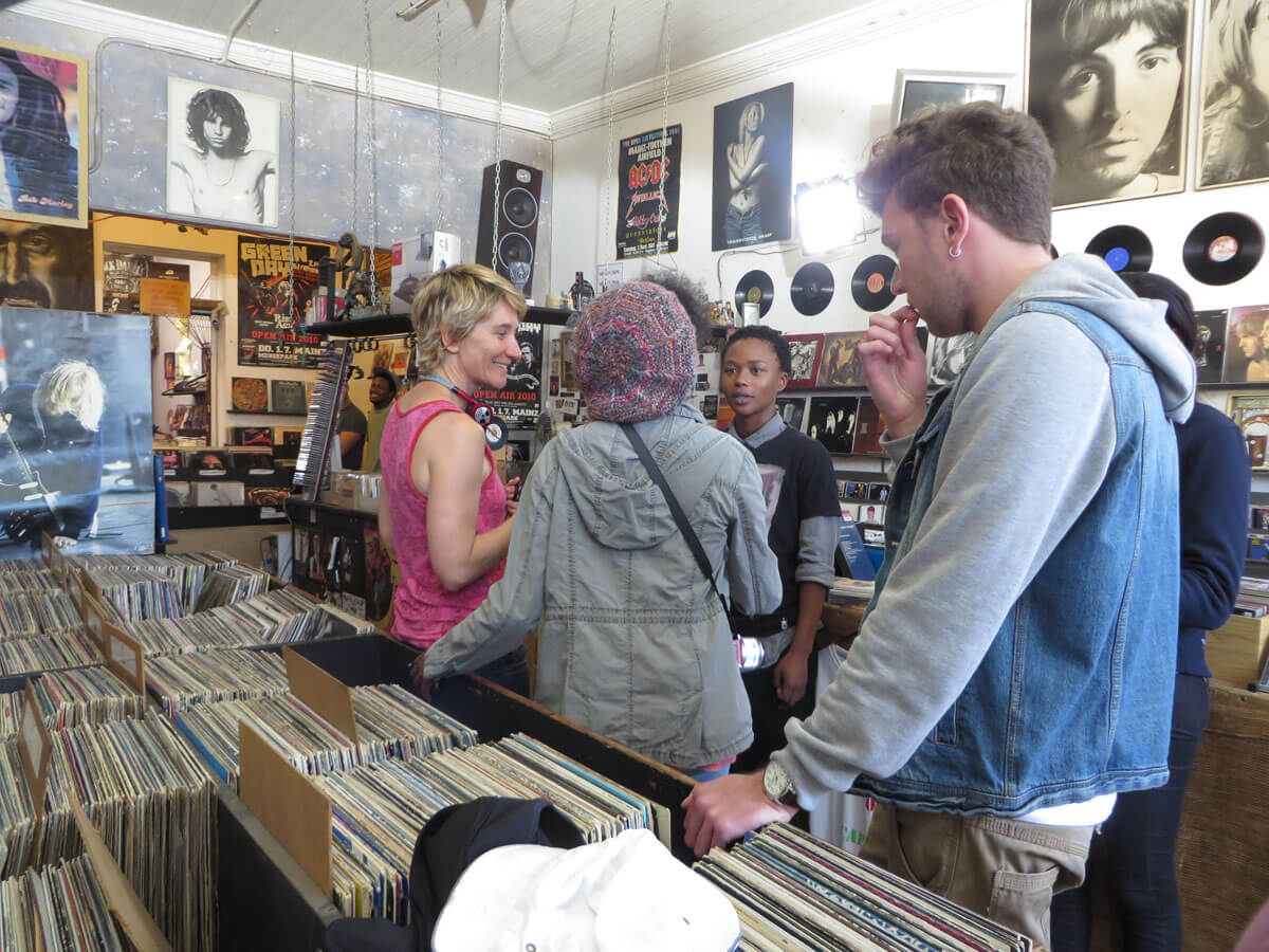 WYWL Obs Record store Dir Stewart talks to Petronella and Thishiwe, Pascual looks on
